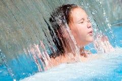 Una ragazza si raffredda fuori sotto la cascata Fotografia Stock