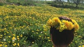 Una ragazza si siede in una sedia di picnic In primavera prato, invaso con i denti di leone di fioritura Sulla testa ? una corona archivi video