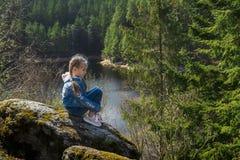 Una ragazza si siede su una scogliera e sugli sguardi alla natura, ragazza che si siede su una roccia e che gode della vista dell fotografia stock libera da diritti