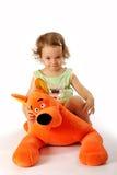 Una ragazza si siede su un cane di giocattolo. Immagine Stock