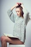 Una ragazza si siede su un cubo Corregge i capelli Legga il libro In un maglione grigio Photoshoot nello studio della foto Immagini Stock
