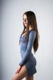 Una ragazza si siede su un cubo Ha messo le sue mani sulle sue ginocchia nude In un maglione grigio Photoshoot nello studio della Fotografia Stock Libera da Diritti