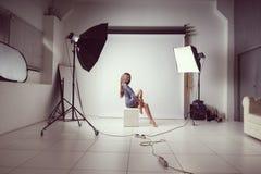 Una ragazza si siede su un cubo Ha messo le sue mani sulle sue ginocchia nude In un maglione grigio Photoshoot nello studio della Immagine Stock