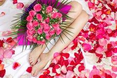 Una ragazza si siede su un letto con un mazzo rosa dei fiori Un regalo per la festa fotografia stock
