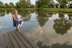 Una ragazza si siede su un palo di un sentiero costiero in un lago con una r da pesca fotografia stock libera da diritti