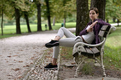 Una ragazza si siede sul banco Immagini Stock