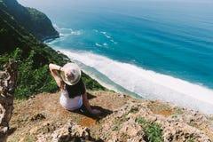Una ragazza si siede sull'orlo di una scogliera bali Fotografie Stock Libere da Diritti