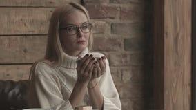 Una ragazza si siede in un caffè e riscalda le sue mani con una tazza di caffè video d archivio