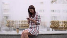Una ragazza si siede vicino ad una fontana nel parco ed utilizza uno smartphone Movimento lento video d archivio