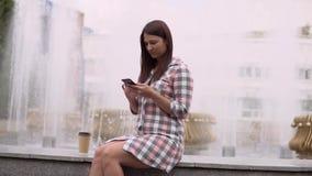 Una ragazza si siede vicino ad una fontana nel parco ed utilizza uno smartphone Movimento lento HD video d archivio