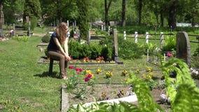 Una ragazza si strizza vicino alla tomba del marito nel cimitero 4K video d archivio