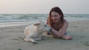 Una ragazza si trova con un cane bianco sulla spiaggia 4K archivi video