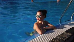 Una ragazza snella ed adulta in un costume da bagno luminoso che riposa nello stagno un giorno soleggiato archivi video