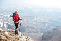 Una ragazza snella in un cappuccio con i bastoni per nordico che cammina con uno zaino e una coperta piegata per rilassamento sta Fotografia Stock