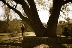 Una ragazza sola che aspetta in un parco Immagini Stock