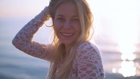 Una ragazza sorride alla macchina fotografica con il sole dietro lei mentre alla spiaggia sul mare video d archivio
