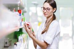 Una ragazza sorridente affascinante con capelli scuri e vetri, portanti un cappotto del laboratorio, prende qualcosa dallo scaffa fotografie stock libere da diritti