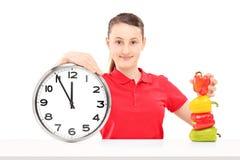 Una ragazza sorridente che tiene un orologio ed i peperoni di parete su una tavola Immagine Stock