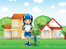 Una ragazza sorridente e la sua bici vicino alle grandi case Immagine Stock