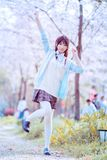 Una ragazza sotto i ciliegi ad aprile fotografia stock