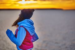 Una ragazza in sport cappello e rivestimento fa un trotto di mattina sull'argine di mattina prima dell'alba del sole fotografia stock