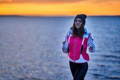 Una ragazza in sport cappello e rivestimento fa un trotto di mattina sull'argine di mattina prima dell'alba del sole immagini stock