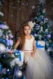 Una ragazza sta aspettando i presente all'albero di Natale fotografia stock