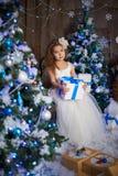 Una ragazza sta aspettando i presente all'albero di Natale fotografia stock libera da diritti