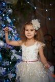 Una ragazza sta aspettando i presente all'albero di Natale Immagine Stock