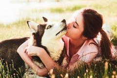 Una ragazza sta baciando un cane della razza del husky fotografie stock libere da diritti