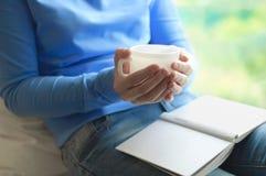 Una ragazza sta bevendo il tè e sta leggendo un libro fotografie stock