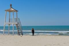 Una ragazza sta camminando intorno alla spiaggia e sta godendo del giorno soleggiato fotografia stock
