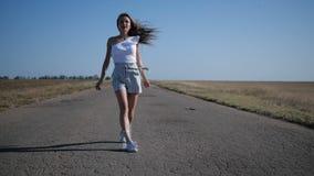 Una ragazza sta camminando su una strada stock footage