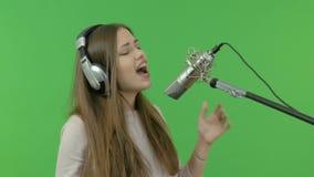 Una ragazza sta cantando in un microfono dello studio Primo piano Su una priorità bassa verde stock footage