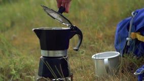 Una ragazza sta cucinando il caffè su un bruciatore a gas in una macchina del caffè del geyser nella natura nelle montagne archivi video