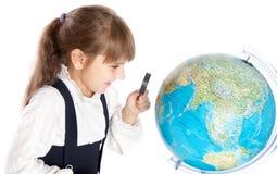 Una ragazza sta esaminando il globo Immagine Stock