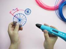 Una ragazza sta giudicando la penna 3d e la retro bici fatte di plastica Immagini Stock