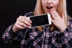 Una ragazza sta giudicando uno smartphone rotto disponibile e sta gridando con indignazione Primo piano fotografia stock