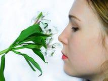 Una ragazza sta odorando i fiori Immagine Stock