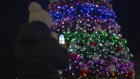 Una ragazza sta prendendo le immagini se stessa su un fondo delle decorazioni di Natale nel parco video d archivio