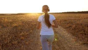 Una ragazza sta preparandosi al tramonto ed ascoltando la musica, la ragazza di sport in cuffie è impegnata nel pareggiare Vista  archivi video