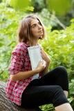 Una ragazza sta sedendosi all'aperto sull'erba in un albero che legge un libro, lo sguardo pensieroso, un giorno di estate all'ap Fotografie Stock