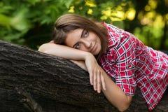 Una ragazza sta sedendosi all'aperto sull'erba in un albero, lo sguardo di nidiata, un giorno di estate all'aperto nel parco Fotografie Stock