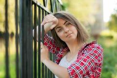 Una ragazza sta sedendosi all'aperto sull'erba in un albero, lo sguardo di nidiata, un giorno di estate all'aperto nel parco Fotografia Stock Libera da Diritti