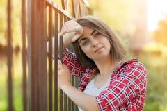 Una ragazza sta sedendosi all'aperto sull'erba in un albero, lo sguardo di nidiata, un giorno di estate all'aperto nel parco Fotografie Stock Libere da Diritti