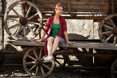 Una ragazza sta sedendosi su un vecchio telega Immagini Stock