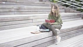 Una ragazza sta sedendosi sulle scale che legge un libro Immagini Stock Libere da Diritti