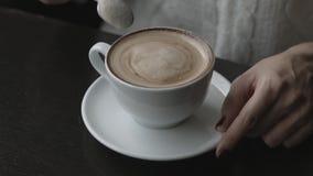 Una ragazza sta sedendosi in un caffè Tè bevente Caffè Zucchero di scalpore Tiene una tazza di caffè in sua mano Primo piano video d archivio
