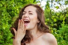 Una ragazza sta sorridendo ai precedenti del parco immagini stock libere da diritti