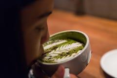 Una ragazza sta sorseggiando il caffè caldo del latte fotografia stock libera da diritti